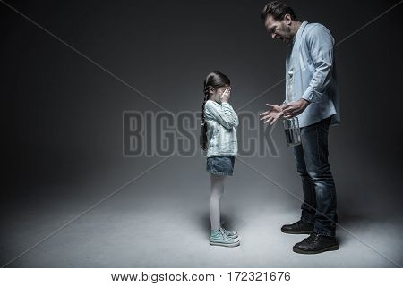 Do not cry. Poor little girl keeping her hands on the eyes wearing jeans skirt and striped shirt standing in semi position over grey background