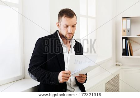 Young concentrated on papers businessman stands near window in modern white office interior. Handsome serious man employee at work reading documents. Lifestyle portrait
