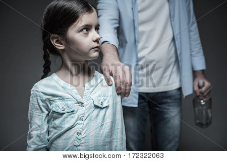 Do not touch me. Astonished little girl keeping her eyes widely opened turning her head aside being afraid of her father