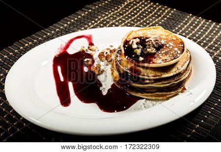 Homemade sweet pancakes with fruit jam on a white plate. Breakfast with stack topped blueberry jam and walnuts