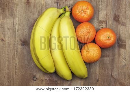 On a wooden surface lie bananas and tangerines
