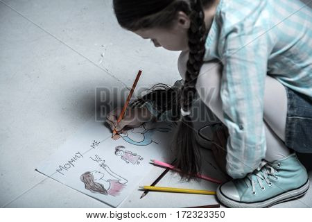 My reality. Attractive girl with two braids from unhappy family holding orange pencil in right hand while making picture