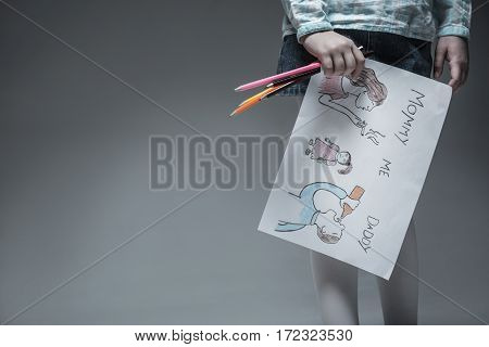 Want to show it. Little girl from unhappy family holding colorful pencils in right hand and picture while standing over grey background