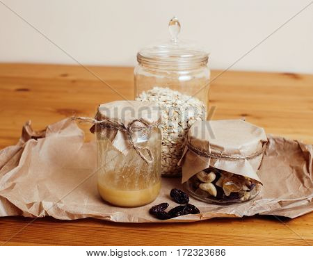 real comfort wooden kitchen with breakfast ingredients close up in glass, honey, oatmeal, milk, muesli, morning food concept
