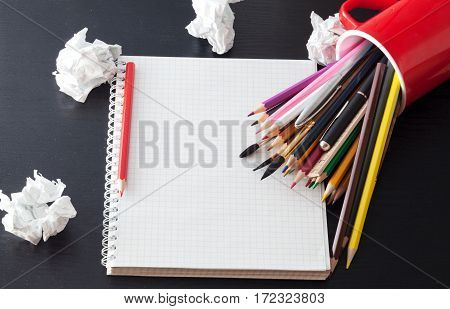 Colour pencils and notebook on a black table