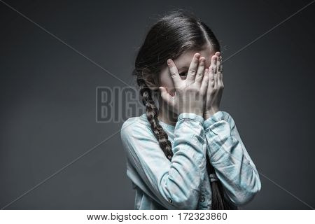 My grief. Attractive girl from unhappy family holding hands on eyes trying to hide herself while standing over grey