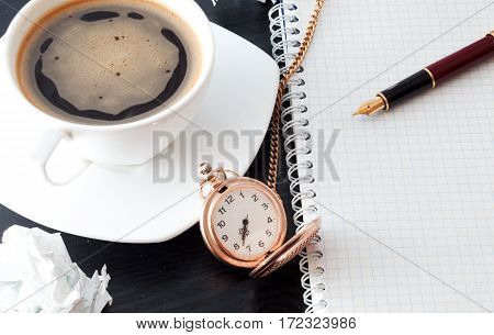 Coffee pen notebook and pocket watch on a black table