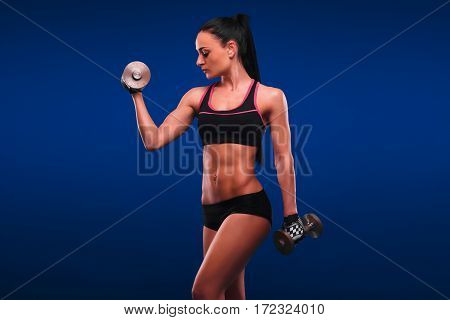 Nice Slim Woman In Azure T Shirt Holds Pair Of Dambells. Isolated On Blue Background.