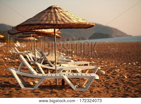 Dreamy beach with sun loungers under parasol on the background of green mountains