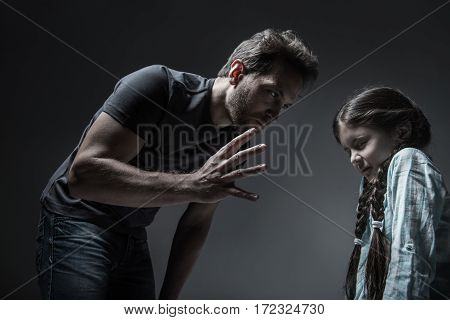 Bad time. Little girl with two braids keeping her eyes closed wearing light blue shirt standing in semi position