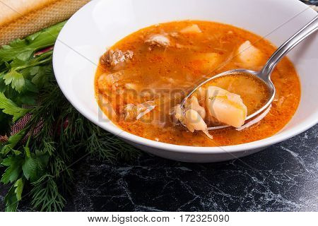 Close Up View Of Plate And Spoon With Red Beetroot Soup Or Borsch On Dark Marble Background. .