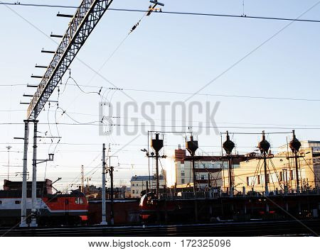 landscape with railway with trains, lot of steel rafters at sunset close up