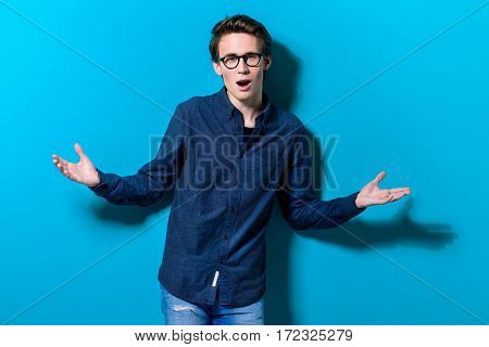 Emotional young man posing over bright blue background. Optics style. Summer fashion.
