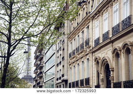french paris street with Eiffel Tower in perspective trought trees, post card view close up