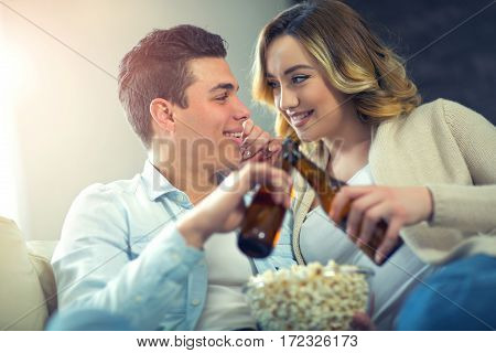 Young couple sitting on the couch in the living room looking at each other and toasting with beer