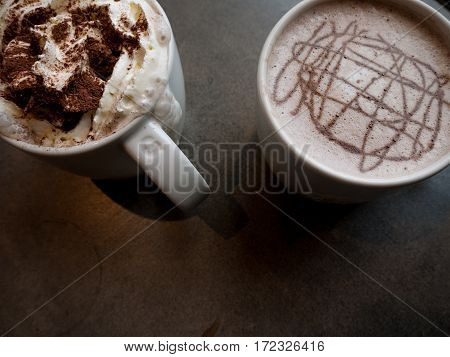Two mugs of coffee and hot chocolate from a tabletop perspective on a granite surface.