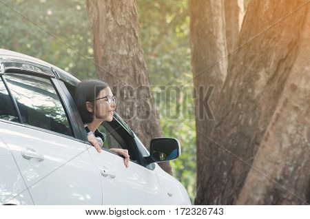 Asian traveler woman breathing fresh nature air from inside the car. Happiness of girl and smiling on vacation.