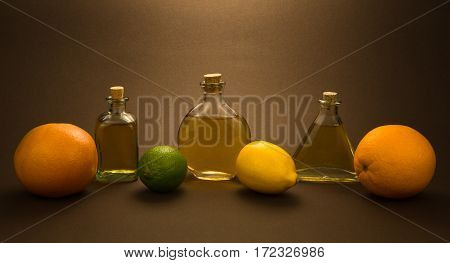 Three vintage glass bottles with lime, lime, grapefruit, lemon and orange on brown background