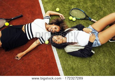 young pretty girlfriends hanging on tennis court, fashion stylish dressed swag, best friends happy smiling together lifestyle