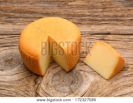 Cheese wheel on wooden table in studio