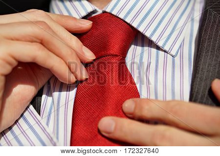 Male hands adjusting a red tie around a neck of a young male in a business suit and lined shirt as a symbol of preparation before a formal event