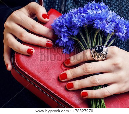 close up portrait of girls manicured hands holding small cute red handbag and cornflower bouquet, lifestyle concept flavor fashion