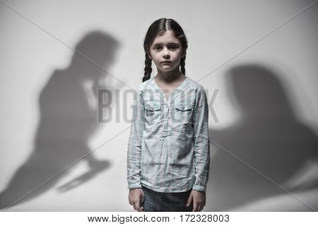 Quarrel in thoughts. Two silhouette of couple worsen the situation in family of depressed girl that standing over grey background holding her arms at side