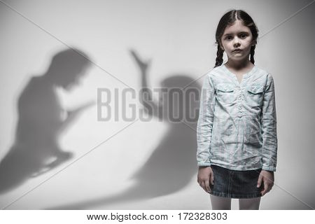 Want better future. Young poor girl having two long braids wearing jeans skirt and blue shirt holding her arms at side