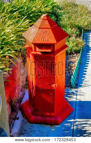 A red 1896 old British style mailbox
