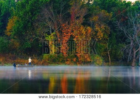 Fisherman in a boat in the autumn season on a foggy lake