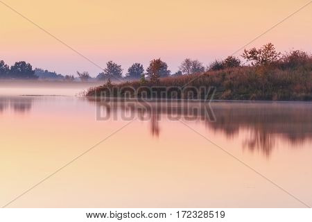 A view of a pond or lake in the autumn. It is taken during a misty foggy morning.