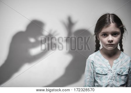 Want to stop it. Portrait of little girl with two braids wearing casual clothes looking at camera