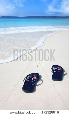Australian flag thongs on the beach with footprints leading into the ocean. Holiday vacation travel leisure unwind