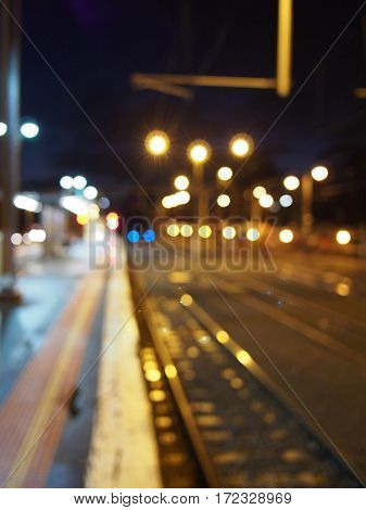 Defocussed railway track with platform and lights at night Melbourne 2016