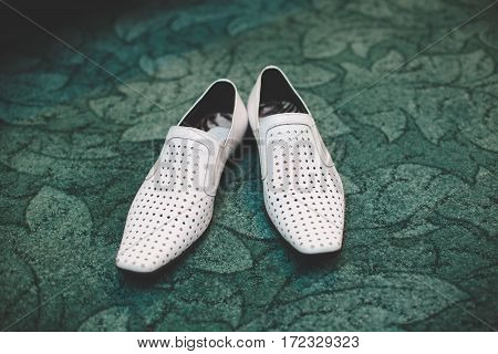 Pair of classic white leather male shoes closeup