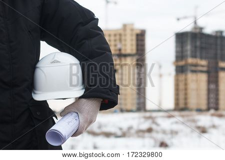 Architect or engineer holding yellow helmet for workers security on background of new highrise apartment buildings and construction cranes on background of winter landscape. Crane lifts load