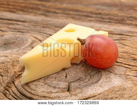 Emmental cheese with grapes on wooden background