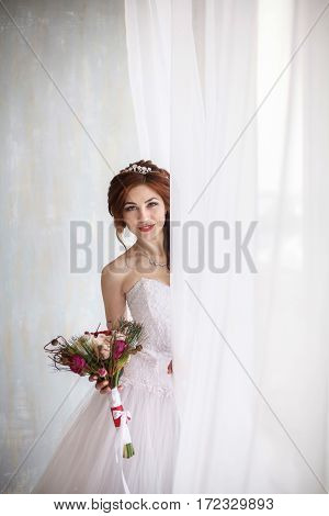 Happy young bride with bridal wedding bouquet near window vertical photo