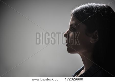 Think about husband. Confident female person pressing her lips keeping her head straight while standing in semi position