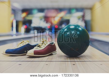 Bowling accessories background. Interior of bowling alley, lane with ball and special shoes closeup, selective focus
