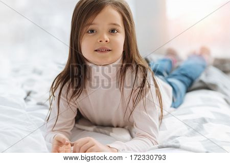 Carefree childhood. Pretty pleasant nice girl lying on the bed and looking at you while being at home