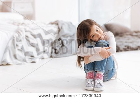 Being at home. Pleasant cute young girl sitting on the floor and tilting her head while looking at you