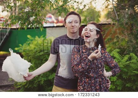 Young happy loving couple with cotton candy having fun and enjoying in park