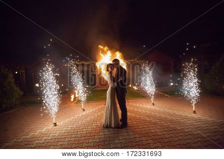 Young groom and bride with two burning hearts fireshow at night wedding or marriage concept