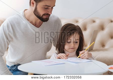 Self development and learning. Pleasant cute diligent girl sitting next to her father and holding a pencil while making a drawing