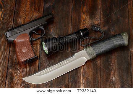 Steel knife flashlight and gun on a dark wooden background close-up