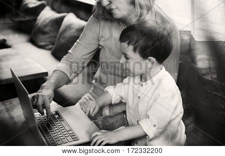 Grandma teaching laptop to nephew
