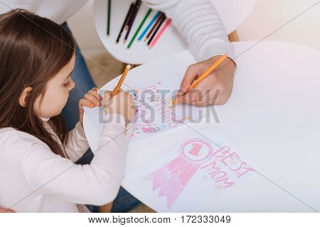 Mothers Day postcard. Nice positive creative girl holding a pencil and drawing a postcard while preparing to Mothers Day