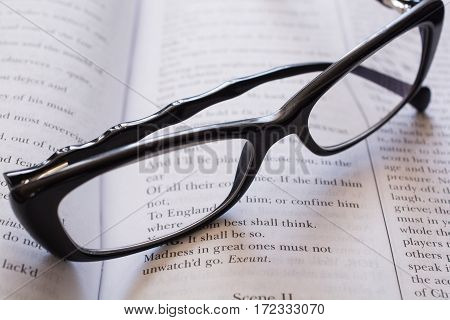 Glasses on the Open Book. Close-Up of Black Glasses.