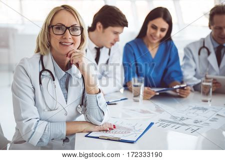 Successful medical doctors are sitting at the conference. Beautiful mature female doctor is looking at camera and smiling